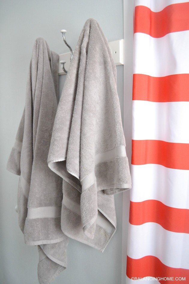 cleaning-organizing-bathroom-with-pedestal-sink-towel-hooks-red-white-striped-shower-curtain