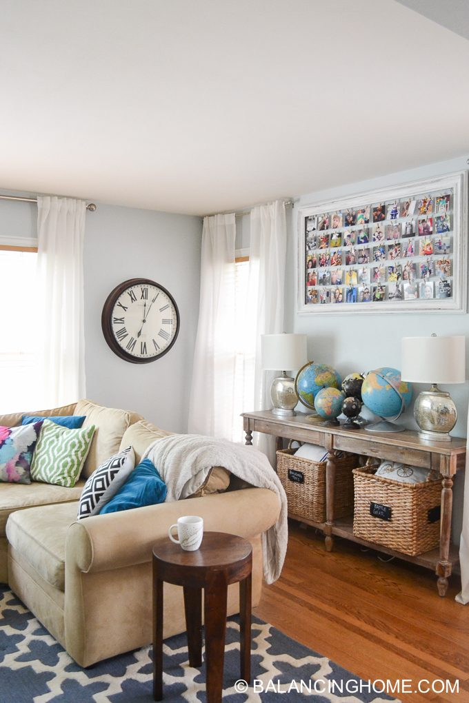 Our living room is decorated with my thrift store globes and a DIY Instagram frame I made from a thrifted frame. A family-friendly space.